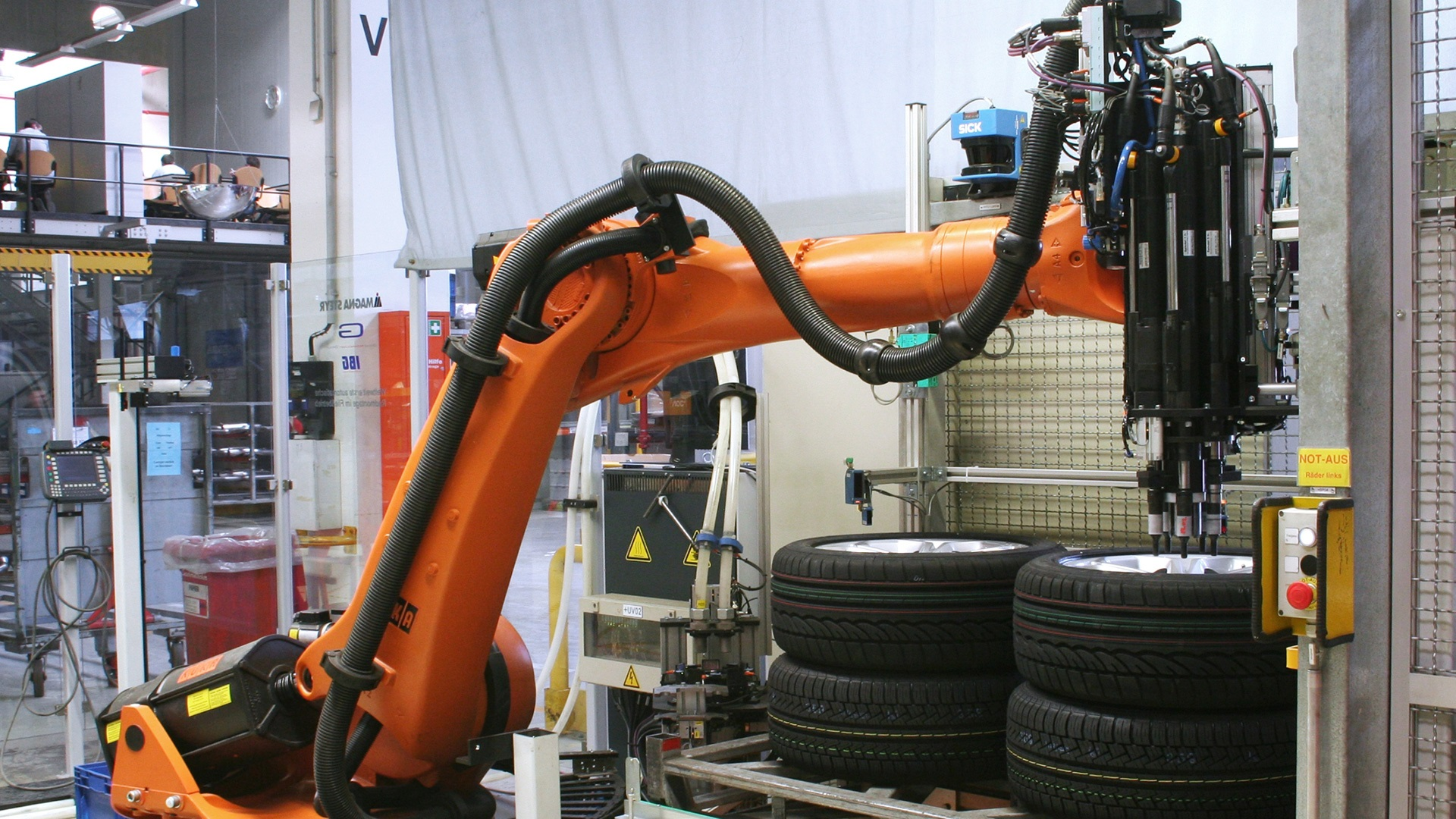 Kuka industrial robots screwing bolts and rims onto a car