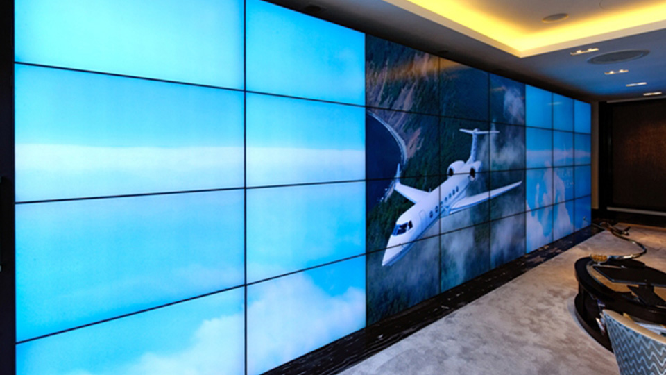 Among many other features, the video wall displays rendered content including an animated background of clouds drifting across the 32 monitors.